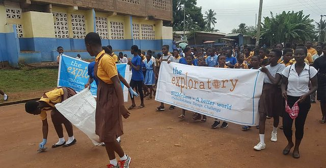 Club members carry banner and garbage bags as clean-up day begins